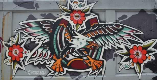 mural of an eagle with wings spread and talons out. A red rose at the top of the mural too. Painted by moveslow (@moveslow)