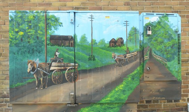 mural painted on a metal box on a sidewalk. Historical picture of the Danforth in 1912 painted by Emilia Jajus. A horse drawn wagon is going down a dirt road, a couple of buildings in the background.