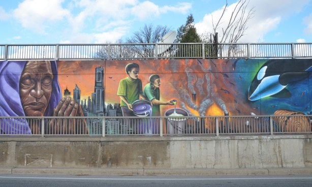 mural with people, city life and comment on mistreatment of the environment