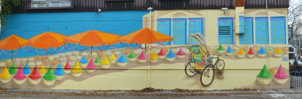 mural in Little India of a decorated bicycle in front of a beige building with orange umbrellas on the left