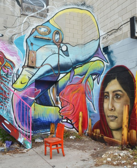 An orange chair sits in front of a corner of a building that is covered with street art. There is a realistic woman's face by kairo and a creature by Nick Sweetman