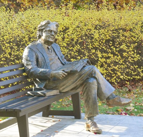 A statue of a man, Northrop Frye, sits on a bench with his legs crossed and an open book on his lap. Another book sits beside him on the bench.
