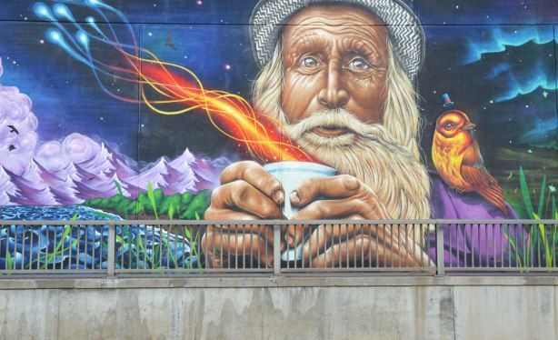 part of a large mural on an underpass in Toronto painted be Essencia Art Collective, an old man with white hair, beard and mustache and wearing a wool hat is holding a paper cup that has fire and steam coming out of it. A bird is sitting on his shoulder