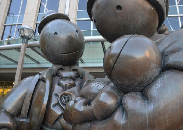 close up of a sculpture by Tom Otterness of a family of three, mother, father and baby in arms. Father is carrying a suitcase. Title of sculpture is Immigrant Family
