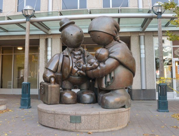 Immigrant Family, a sculpture by Tom Otterness, a father mother and baby in arms.