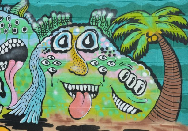 street art mural of a blob creature in green with two faces, one with tongue sticking out and one with three eyes. It is beside a palm tree on a beach.