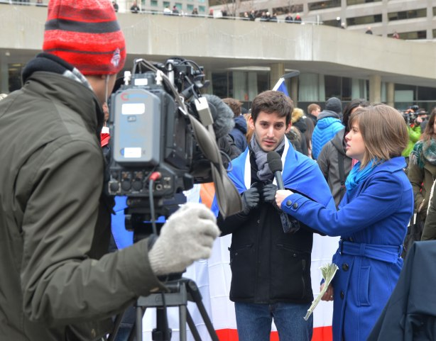 A young man with a French flag draped over his shoulders is being interviewed for TV