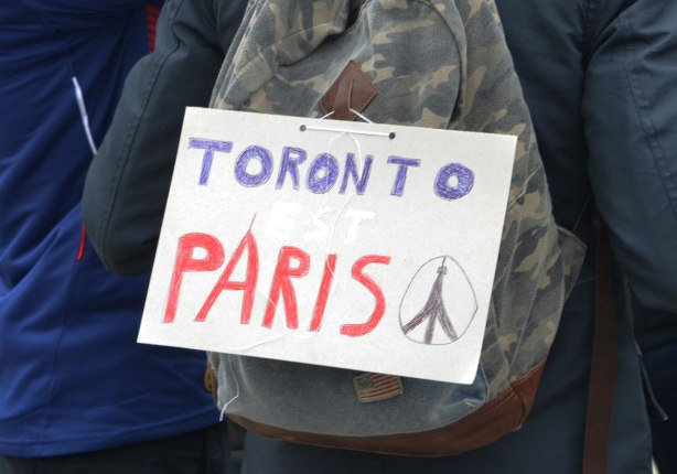 A sign on a backpack that says Toronto est Paris. Written in blue, white and red