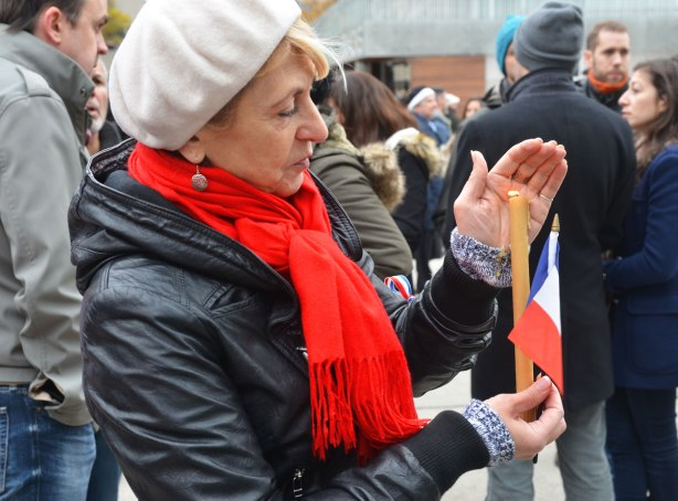 A woman in a white beret and red scarf is holding a lit candle and a small French flag