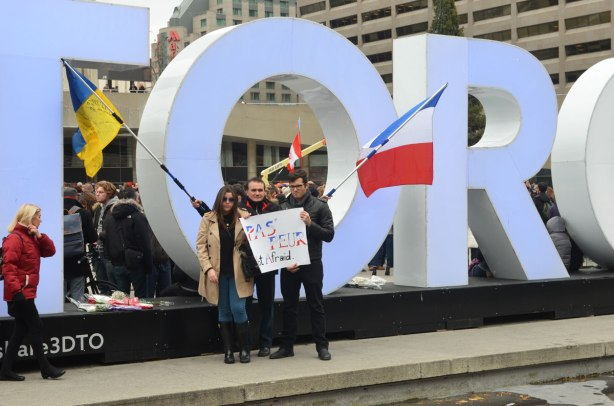 """Three people standing in front of the 3D Toronto sign, holding a French flag and a large sign that says """"Pas Feur, no fear"""""""