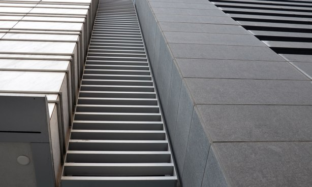 close up shot, taken looking up the wall of a skyscraper, looks like rungs of a ladder in metal on concrete