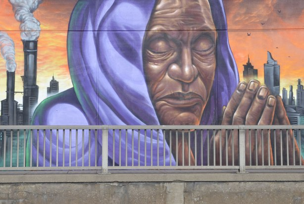 mural of a person praying, hands together, eyes closed, wearing a purple shawl over their head
