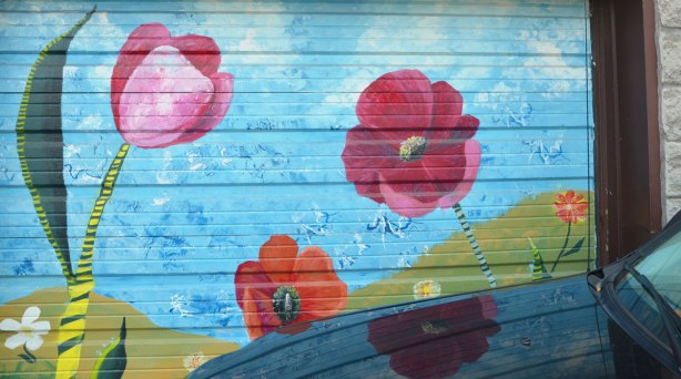 garage door mural of red poppies by bright blue sky.