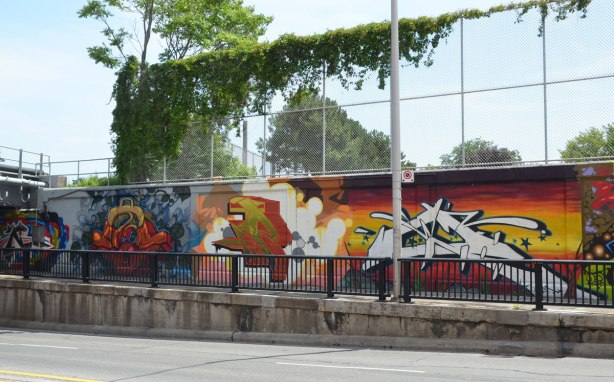 part of a large collection of street art paintings on a wall of a railway underpass on Bloor St. West as seen from across the street,