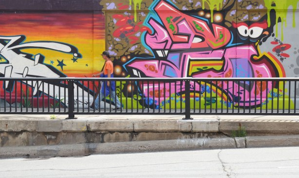 part of a large collection of street art paintings on a wall of a railway underpass on Bloor St. West as seen from across the street, a man is walking past