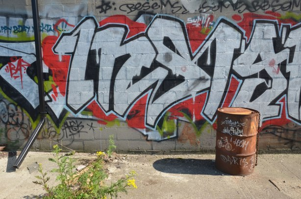 A black and white tag on red background, with the words happy bday nektar written in the corner. In front of the wall is a rusted metal oil drum with some graffiti on it in white including a very meticulously drawn small white bicycle.