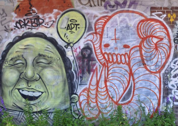 graffiti of a greenish man's face, closed eyes, laughing with mouth open, beside him is a greyish white elephant outlined in red with long tusks and trunk