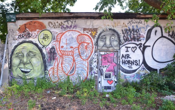 a wall covered with graffiti, a large bald man's head, a red and white elephant, a lovebot, a black line drawn bird saying I love air horns