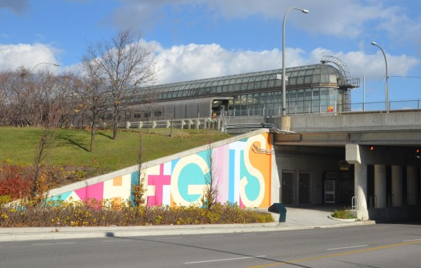 part of a mural on an underpass. There are four parts to the mural and each part is word painted in large capital letters in many colours - the word heights, with the south end of Yorkdale subway station in the picture