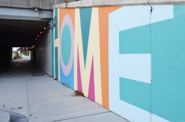 part of a mural on an underpass. There are four parts to the mural and each part is word painted in large capital letters in many colours - the word home