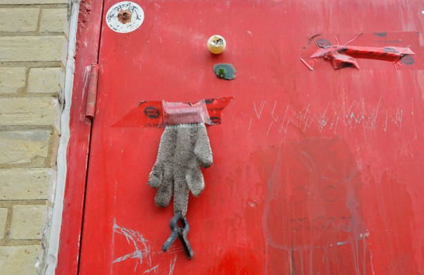 A red door with some items attached to it - a squished ping pong ball, an old dirty grey glove with a clip attached to the end of one finger