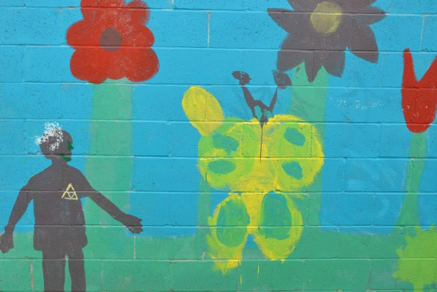 mural painting on a wall, bright blue background, a person in silhouette, a red flower, a yellow and green butterfly, and a red tulip