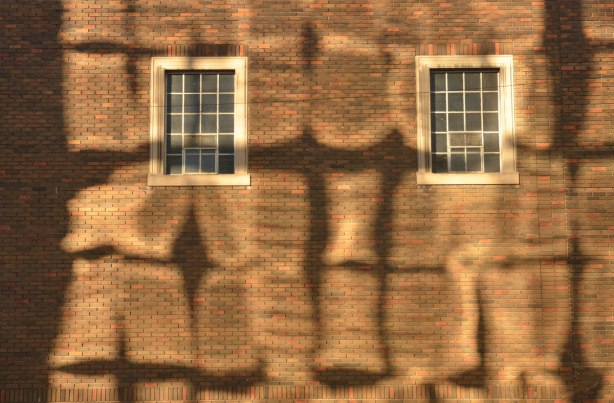 brick building with wavy shadows on it cast by the sun being reflected off the glass building across the street