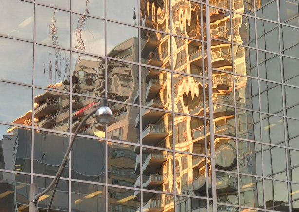 many curved and disjointed reflections of buildings in a tall glass building. Afternoon sun so there's a yellowish tint to the reflections