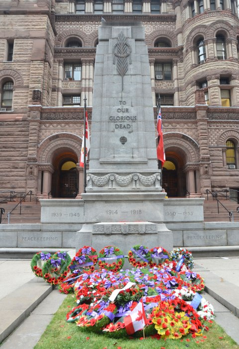 The cenotaph in front of Old City Hall in Toronto, with a collection of wreaths that have been laid at the bottom of it.