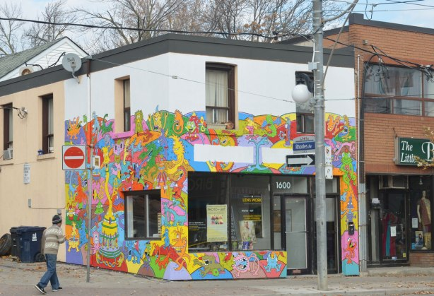 A store on the corner of Gerrard and Rhodes in Toronto where the front and side of the building are covered with multicoloured street art.