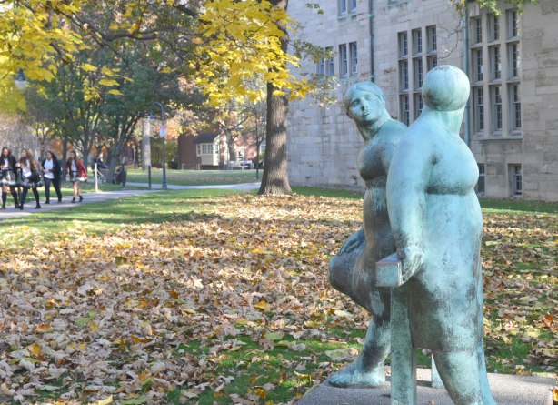 A blueish bronze statue of two overweight women standing facing each other beside a stone building on the University of Toronto campus. It is autumn and there are leaves on the ground. A group of girls is walking in the background.