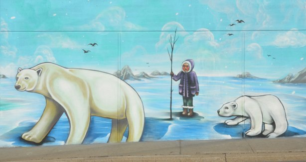arctic scenes as part of a larger street art mural on an underpass in Toronto - a person in a purple parka holding a little tree, standing in ice between two polar bears
