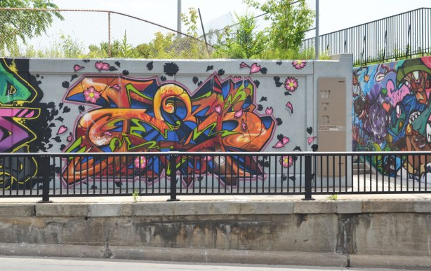 looking across the street at a mural painted on the side wall of an underpass. Bright, multicoloured, curved lines and shapes. The entrance to the west toronto railpath is also in the picture