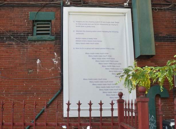 words in dark blue written on a white board that is fastened to a brick wall, behind a rust coloured metal fence