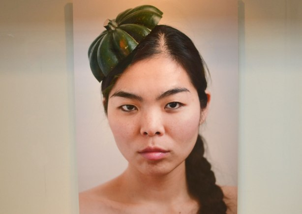 A picture of a photo of an Asian woman with her hair in a braid, a stern expression on her face, and the top of an acorn squash on her head in place of a hat
