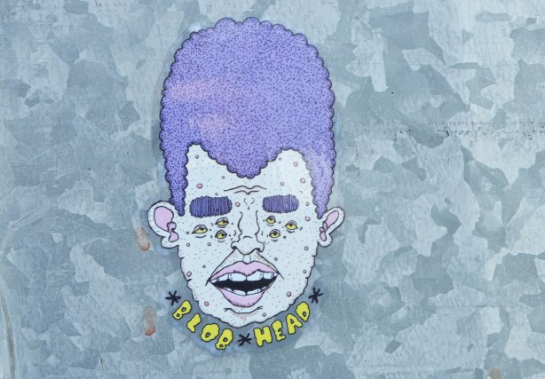 sticker on a grey metal pole. head with the words Blob Head written underneath. Purple hair, open mouth, pink lips, teeth showing, purple bushy eyebrows and three small eyes where each eye should be (six eyes in total)