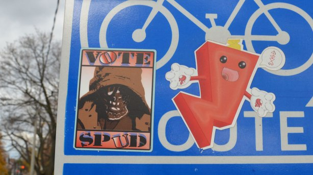 close up of two stickers on a blue and white bike route sign. One sticker is a brown one with the words Vote Spud and a picture of skull wearing a floppy hat. The other is a red cartoon character
