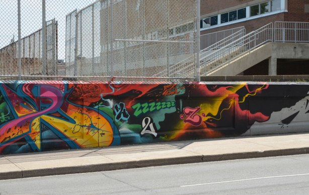 wall of street art beside a sidewalk.  Tall chain link fence above the wall and a brick school building behind the fence