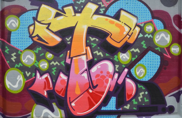 street art painting on a wall based around the letter t, lower case