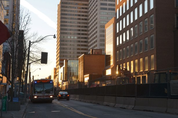 very late afternoon sun, as it disappears behind buildings, looking down a street, sun is reflecting off some windows, a large part of the street is in shadow, a TTC is there, with its lights on, some construction on the street, some cars,