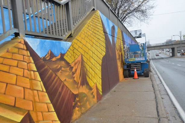 looking down a sidewalk. A wall on the left has been painted with gold orange and brown pyramids, a lift is in the middle of the sidewalk, a busy street, Lawrence Ave, is to the right.