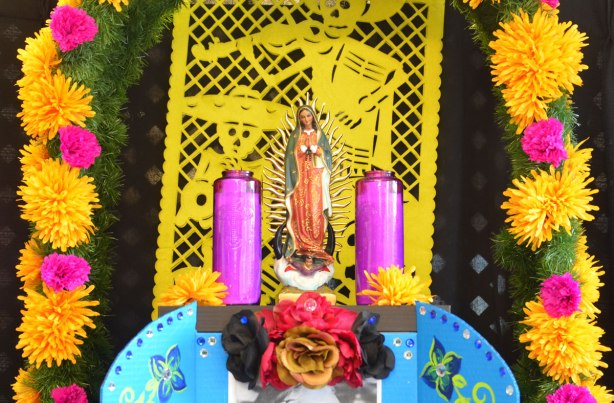 a statue of mary with pink candles on either side of her. A yellow day of the dead paper cut out is behind her. Strings of yellow, orange and pink flowers are also on either side of her.