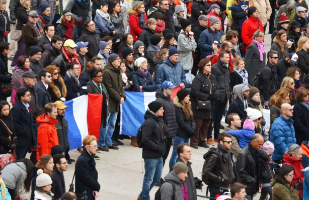A crowd of people standing at Nathan Phillips Square listening to speeches. Some people hold two large French flags.