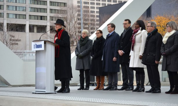Carolyn Bennett, Liberal MP, speaks at a gathering at Nathan Phillips Square that pays tribute to the city of Paris. A lineup of other people waiting to talk, including John Tory, mayor, is standing behind her.