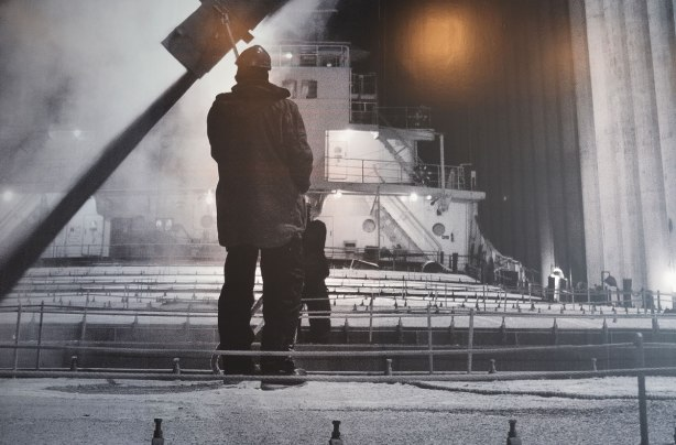 close up of part of a very large black and white photograph of a man standing on the deck of a lake freighter at night in the winter
