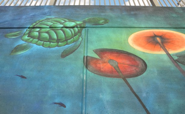 street art mural of a turtle swimming by some lily pads in the water, as seen from below