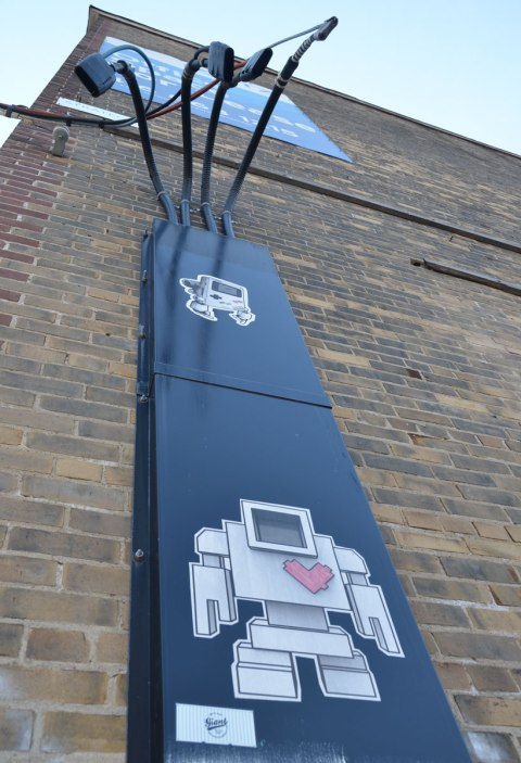 two lovebots on a blue metal structure on a brick wall. The top one is a gameboy lovebot. The bottom one is the usual robot lovebot.