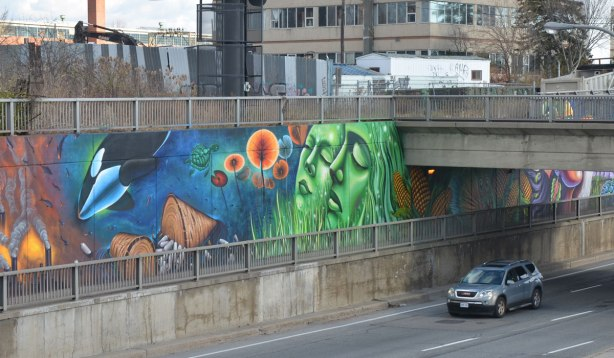 car driving under a bridge and past a mural painted on the walls of the underpass, two large green women's faces tilted upwards with eyes closed