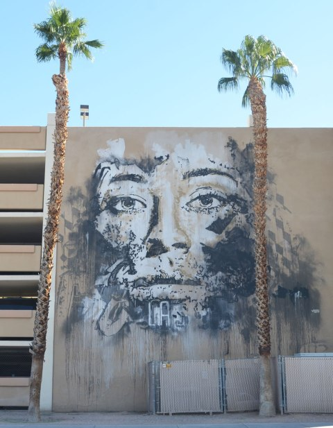 A large man's face on the side of a parking structure, with two tall palm trees