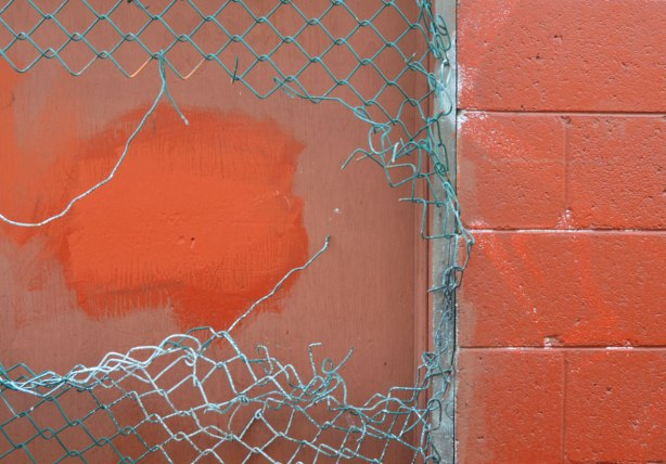 A broken vinyl covered chainlink fence in front of a red wall that is part concrete block and part wood